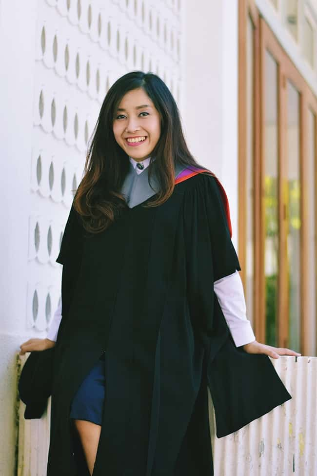 Smiling college graduate wearing graduation robe